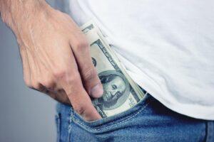 Man puts money into his pocket.
