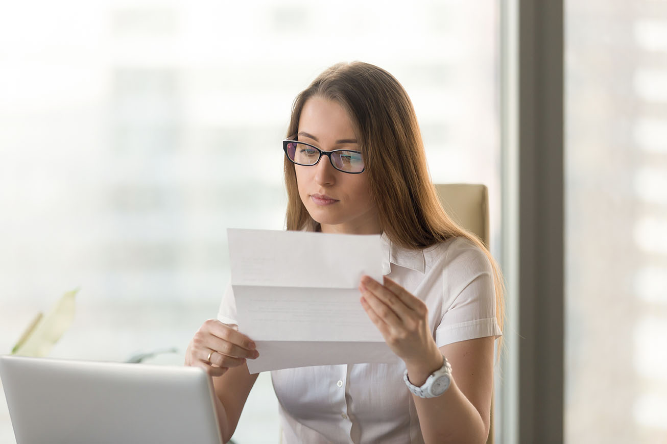 Businesswoman reading official document at workplace