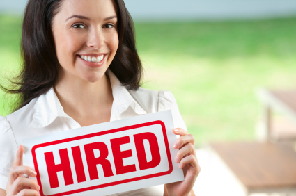 Attractive woman holding hired sign. Blurred background